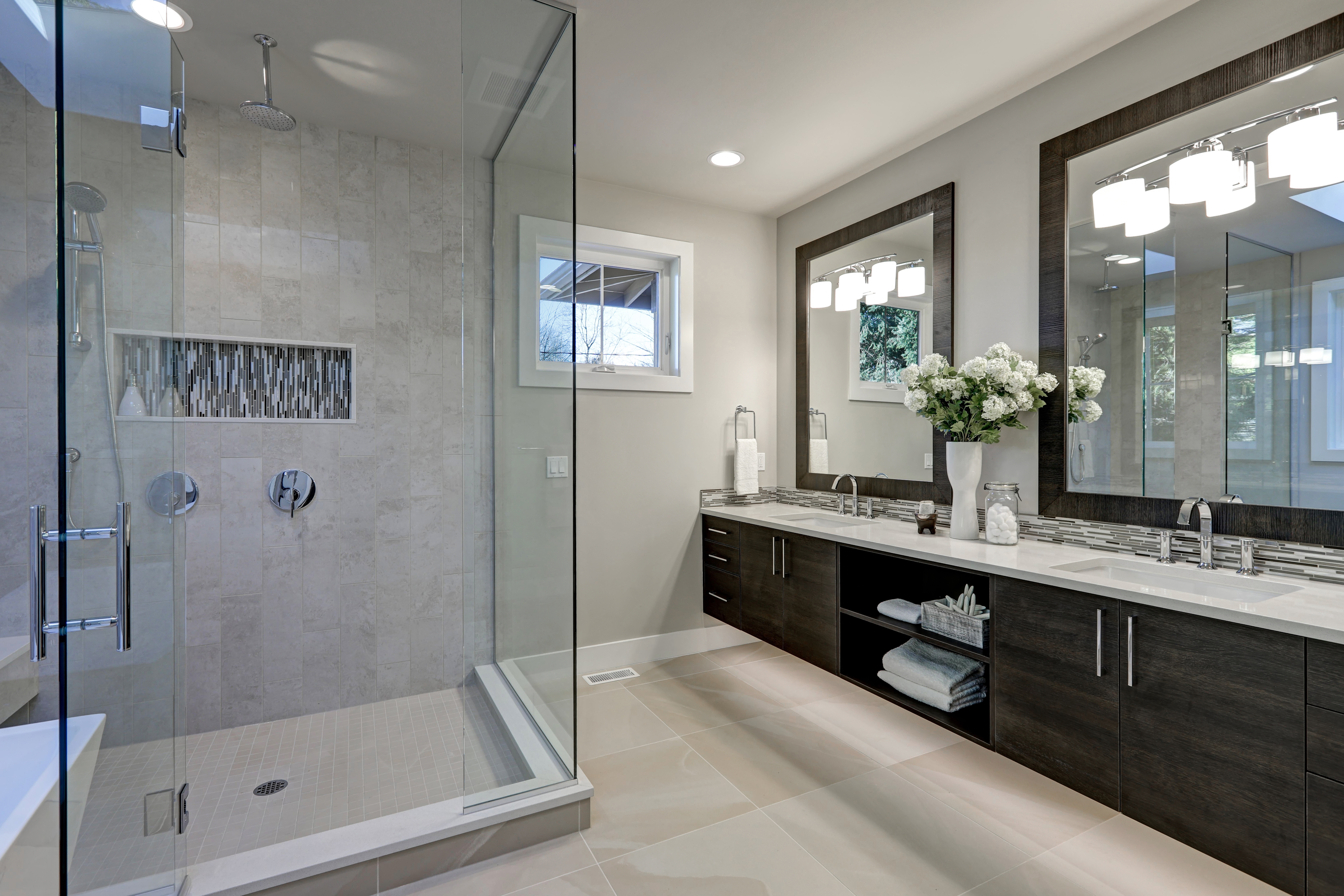 Spacious bathroom in gray tones with heated floors walk-in shower double sink vanity and skylights. Northwest USA