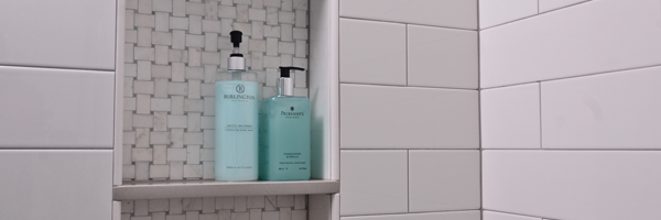 White subway tile shower with marble inset shampoo caddy