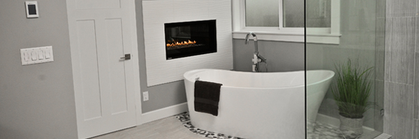 Master bathroom showing a freestanding bath tub, tile shower and fireplace in Aloha, Oregon