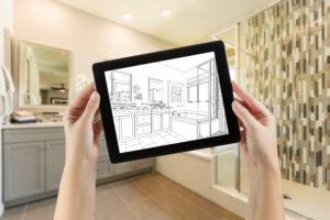 Hands Holding Computer Tablet with Master Bathroom Photo on Screen and Drawing Behind.