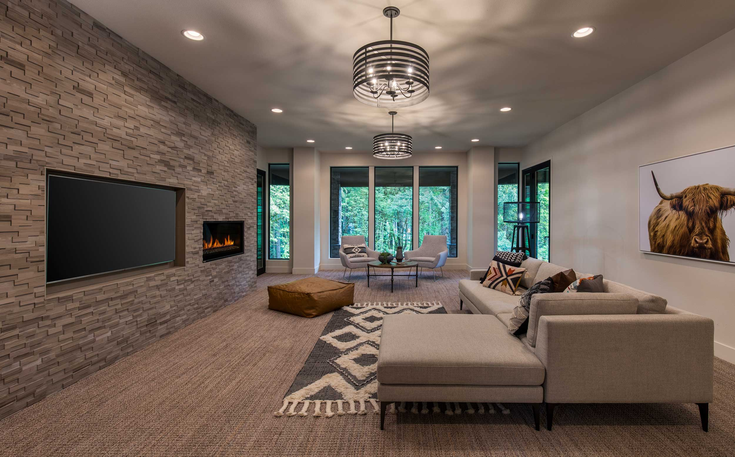 Basement media room with modern TV and fireplace wall.